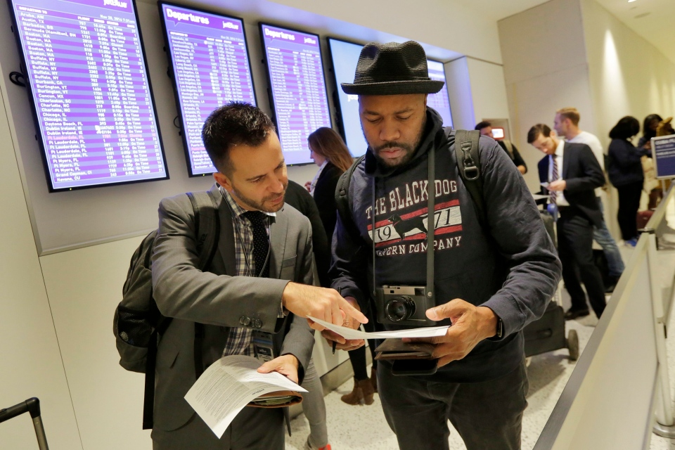 David McGraw, left, and Derrick Jones, both from New York, look over their paperwork while waiting to check in for JetBlue's inaugural flight from New York's John F. Kennedy International Airport to Havana, Monday, Nov. 28, 2016. (AP / Richard Drew)