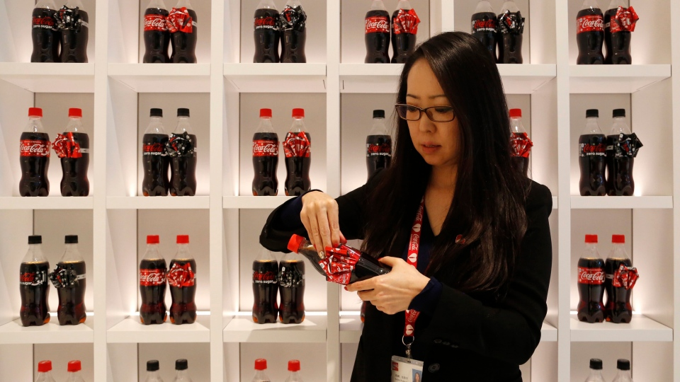In this Nov. 9, 2016 photo, Kanako Kumazaki, group manager at Coca-Cola Japan, demonstrates the ribbons on the Coke bottles that are special for the holiday season at the Coca-Cola Japan office in Tokyo. (Yuri Kageyama/AP Photo)