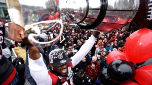 Ottawa RedBlacks Nick Taylor raises the Grey Cup over his head as he rides on a float at a parade celebrating the team's victory over the Calgary Stampeders, Tuesday, Nov. 29, 2016 in Ottawa. (Justin Tang / THE CANADIAN PRESS)