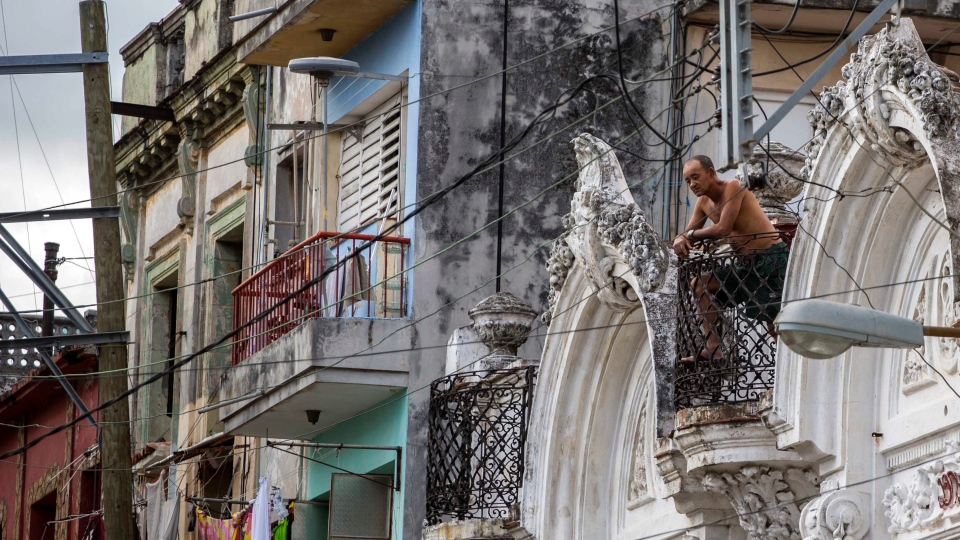 A man looks out from his balcony in Havana, Cuba, Sunday, Nov. 27, 2016. (AP Photo / Desmond Boylan)