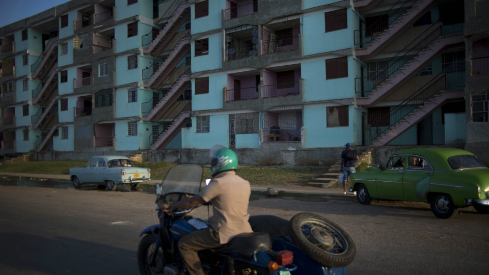 A man drives his motorcycle with a sidecar next to buildings of the Alamar neighbourhood in Havana, Cuba on April 12, 2014. (AP / Ramon Espinosa)