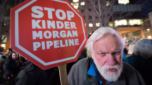Paul George holds a sign during a protest against the Kinder Morgan Trans Mountain Pipeline expansion project, in Vancouver, B.C., on Tuesday November 29, 2016. THE CANADIAN PRESS/Darryl Dyck