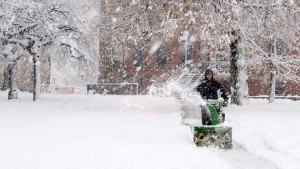 A man uses a snow blower in front of the Coles building in downtown Charlottetown on Nov. 30, 2016. (John Morris / THE CANADIAN PRESS)
