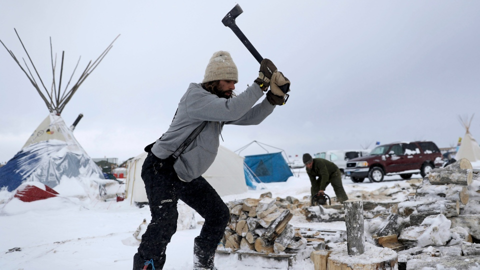 In this Tuesday, Nov. 29, 2016 photo, Blackhorse Shasta, of Oregon, chops wood on the Oceti Sakowin camp where people have gathered to protest the Dakota Access pipeline near Cannon Ball, N.D. (David Goldman/AP Photo)
