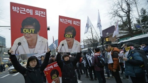 Protesters with pictures of South Korean President Park Geun-hye march toward the presidential house during a rally calling for Park to step down in Seoul, South Korea on Wednesday, Nov. 30, 2016. (AP / Ahn Young-joon)