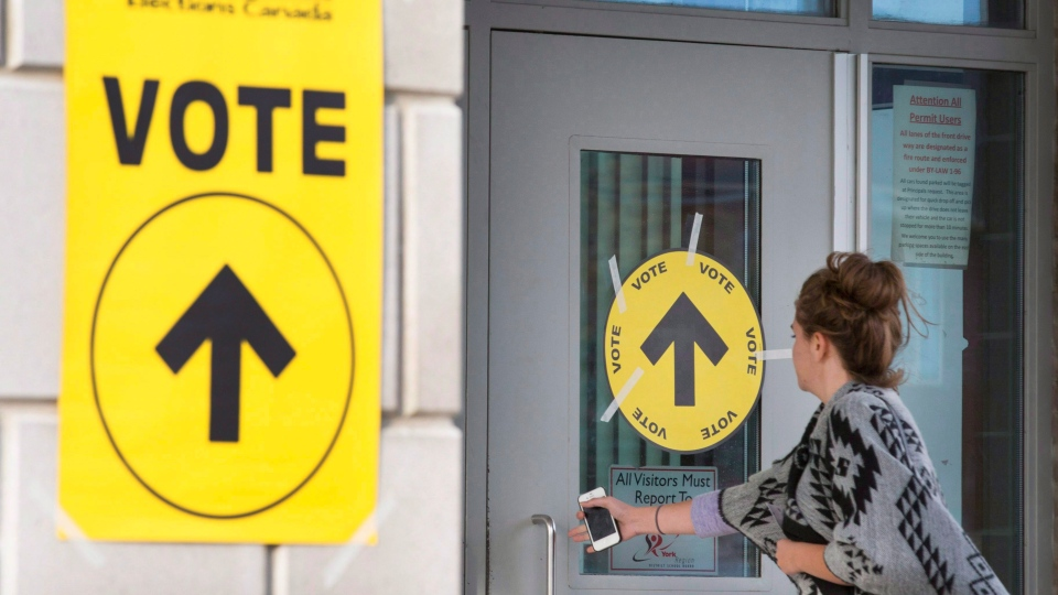 A woman enters Maple High School in Vaughan, Ont., to cast her vote in the Canadian federal election on Monday, Oct. 19, 2015. THE CANADIAN PRESS/Peter Power
