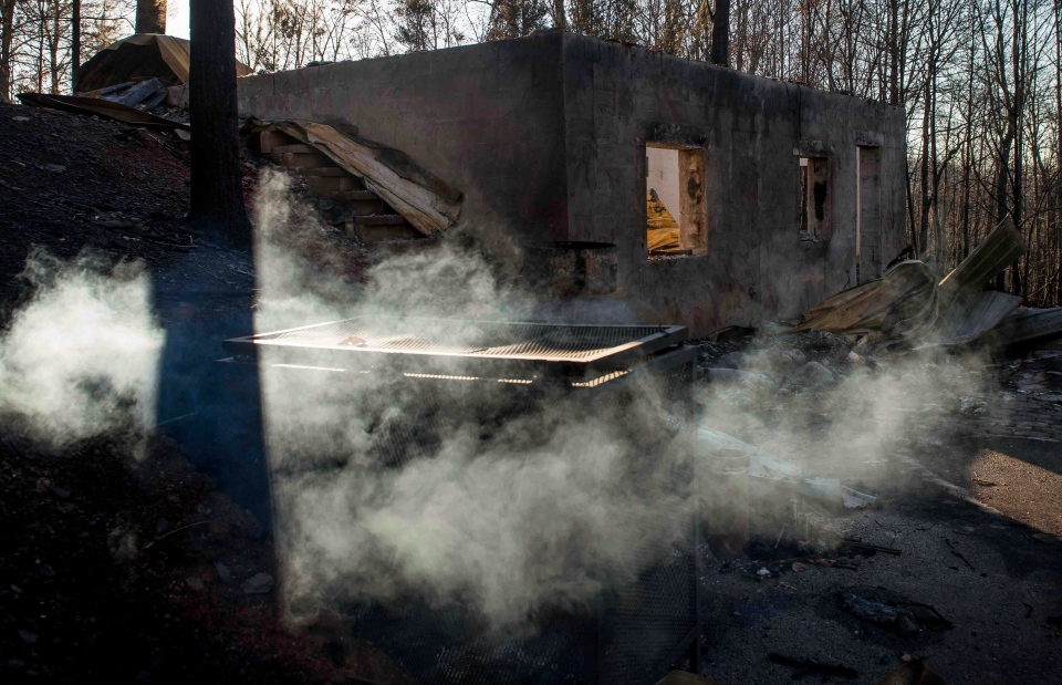 Smoke billows from the remains of a home on the northern outskirts of Gatlinburg, Tenn., Thursday, Dec. 1, 2016. (Andrew Nelles/The Tennessean via AP)