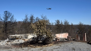 An Air National Guard helicopter flies over Gatlinburg, Tenn., Thursday, Dec. 1, 2016 searching for problems following Monday's devastating wildfire. (Michael Patrick/Knoxville News Sentinel via AP)