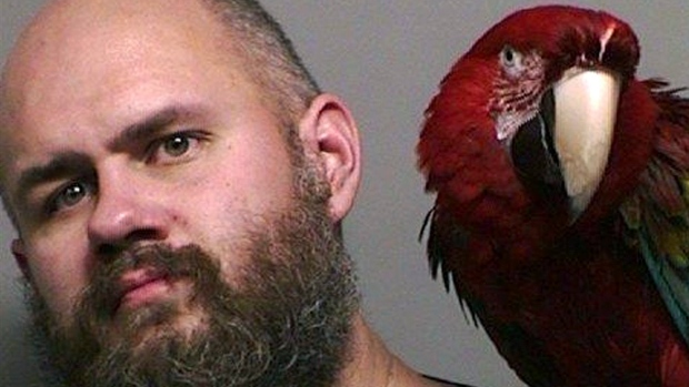 """This booking photo provided by the Washington County Sheriff's office taken in Hillsboro, Ore., Thursday, Dec. 1, 2016, shows Craig Buckner with his macaw, named """"Bird."""" (Multnomah County Sheriff's Office via AP)"""