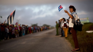 A woman holds a Cuban flag while waiting for the ashes of Cuban leader Fidel Castro driven along the central road in Las Tunas province, Cuba, Friday, Dec. 2, 2016. Castro's ashes are in a four-day journey across Cuba from Havana to their final resting place in the eastern city of Santiago. (AP Photo/Rodrigo Abd)