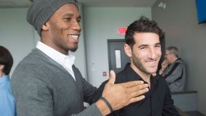 Montreal Impact striker Didier Drogba, left, has a laugh with teammate Ignacio Piatti as he says goodbye after the end of season news conference, in Montreal, on Friday, Dec. 2, 2016. (THE CANADIAN PRESS/Ryan Remiorz)