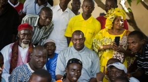 Gambians gather for a photo around president elect Adama Barrow, center, at his residence in Yundum, Gambia, Saturday Dec. 3, 2016. Gambia's newly elected president Barrow says he will free the country's political prisoners, reverse the former administration's decision to leave the International Criminal court and lead a transition government for only three years. (AP Photo/Jerome Delay)
