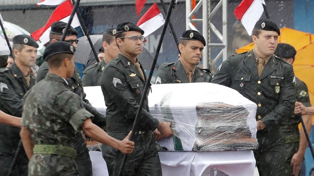 Military carry a coffin with the remains of Chapecoense soccer team victims, during an arrival ceremony in Chapeco, Brazil, Saturday, Dec. 3, 2016. (AP Photo/Andre Penner)