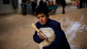 A Syrian boy displaced with his family from eastern Aleppo holds a sandwich and bread bag in the village of Jibreen south of Aleppo, Syria, Saturday, Dec. 3, 2016. (Hassan Ammar/AP Photo)
