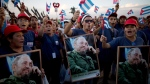 Holding pictures of the Cuban leader, people chants slogans before a mass rally honoring Fidel Castro at the Antonio Maceo plaza in Santiago, Cuba, Saturday, Dec. 3, 2016. Castro's ashes arrived in Santiago to be buried after a four-day journey across Cuba from Havana. (AP Photo/Rodrigo Abd)