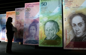 In this Oct. 24, 2007 file photo, a woman looks at oversized versions of the Venezuelan currency, coined the 'Strong Bolivar' in Caracas, Venezuela. (AP / Howard Yanes)