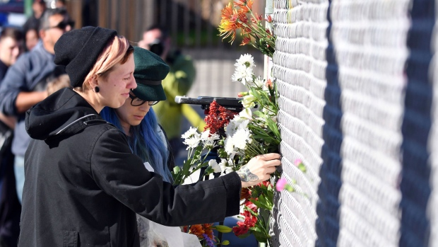 People place flowers near the scene of a warehouse fire Saturday, Dec. 3, 2016, in Oakland, Calif. A deadly fire broke out during a rave at the converted warehouse in the San Francisco Bay Area. (AP Photo/Josh Edelson)