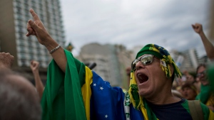 A man shouts slogans during a protest against corruption on Copacabana beach, in Rio de Janeiro, Brazil, Sunday, Dec. 4, 2016. Thousands of protesters are crowding Rio de Janeiro's beachfront to express disgust with public corruption and to support the judges and prosecutors pursuing those crimes. Protests are also under way Sunday in other Brazilian cities. (Silvia Izquierdo/AP Photo)