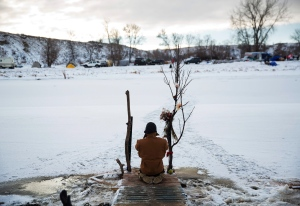 Army veteran Nick Biernacki, of Indiana, prays at the Cannonball River at the Oceti Sakowin camp where people have gathered to protest the Dakota Access oil pipeline in Cannon Ball, N.D., Sunday, Dec. 4, 2016. (AP Photo/David Goldman)