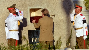 """Cuba's President Raul Castro places the ashes of his older brother Fidel Castro into a niche in his tomb, a simple, grey, round stone about 15 feet high at the Santa Ifigenia cemetery in Santiago, Cuba, Sunday Dec.4, 2016. The niche was then covered by a plaque bearing the single name,""""Fidel.""""(Marcelino Vazquez Hernandez/ACN via AP)"""