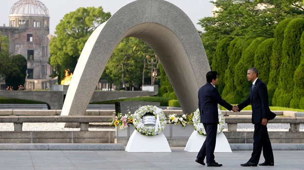 FILE - In this May 27, 2016 file photo, U.S. President Barack Obama, right, shakes hands with Japanese Prime Minister Shinzo Abe at Hiroshima Peace Memorial Park in Hiroshima, western Japan, as Obama became the first sitting U.S. president to visit the site of the world's first atomic bomb attack. (AP Photo/Carolyn Kaster, File)