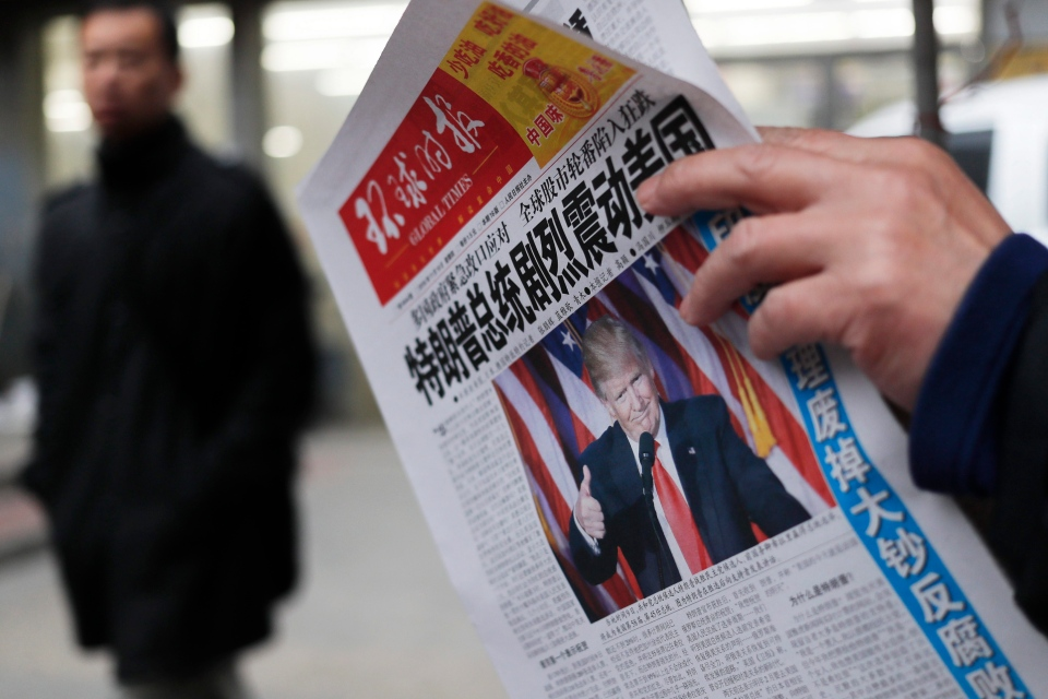 In this Nov. 10, 2016 file photo, a man reads a newspaper with the headline that reads 'U.S. President-elect Donald Trump delivers a mighty shock to America' at a newsstand in Beijing. (AP / Andy Wong)