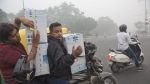 In this Sunday, Nov. 6, 2016 photo, people ride a motorcycle carrying air purifiers at a traffic intersection surrounded by a thick layer of smog in New Delhi, India. (AP / Manish Swarup)
