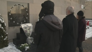White roses are placed in front of a memorial plaque at Ecole Polytechnique on Dec. 6, 2016