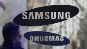 A man passes by the Samsung Electronics Co. logos at its headquarters in Seoul, South Korea on Dec. 12, 2013. (AP / Ahn Young-joon)