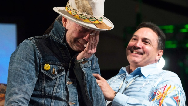 Assembly of First Nations Chief Perry Bellegarde holds an emotional Gord Downie as he given an aboriginal name during a ceremony honouring Downie at the AFN Special Chiefs assembly in Gatineau, Que., Tuesday, Dec. 6, 2016. (Adrian Wyld / THE CANADIAN PRESS)