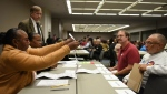 Recount workers, from left, Sandra Sykes and Jessica Thornton show Donald Trump observer Walter Crutis and Hillary Clinton observer Norman Scott a ballot as Trump campaign attorney Dennis Flessland looks on during the recount of Wayne County ballots in the statewide presidential election recount at Cobo Hall in Detroit Tuesday morning, Dec. 6, 2016. (Tanya Moutzalias / The Grand Rapids Press)