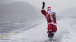 Steve Austin is dressed as Santa Claus as he waterskis along Indian Arm in North Vancouver, B.C. on Dec. 23, 2015. (Jonathan Hayward / THE CANADIAN PRESS)