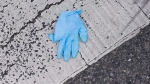 A rubber glove is seen discarded on the ground near the scene of a shooting on Danzig Street in Toronto, on July 17, 2012. (Aaron Vincent Elkaim / THE CANADIAN PRESS)