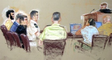 Omar Khadr, far left, sits flanked by two civilian and one military lawyer, inside the courtroom during a U.S. Military Tribunal arraignment at Guantanamo U.S. Naval Base, Cuba. (AP / Janet Hamlin)