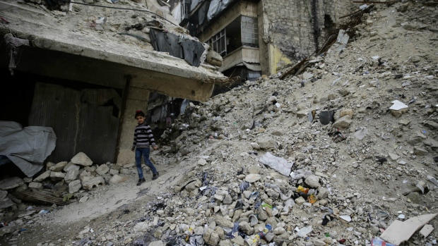 A Syrian girl walks amid the wreckage of damaged buildings and shops in the western city of Aleppo, Syria on Monday, Dec. 5, 2016. (AP / Hassan Ammar)
