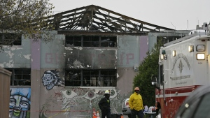 A pair of Oakland fire officials walk past the remains of the Ghost Ship warehouse fire in Oakland, Calif. on Wednesday, Dec. 7, 2016. (AP / Eric Risberg)