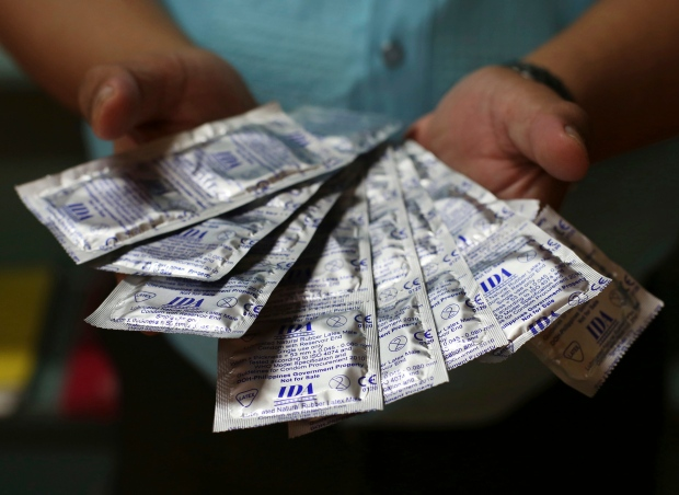 A Filipino health worker shows condoms that are given for free to the public by the Department of Health in Manila, Philippines, on Thursday, Dec. 8, 2016. (AP Photo/Aaron Favila)