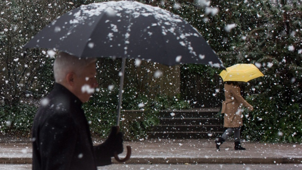 Pedestrians carrying umbrellas walk along Robson Street as snow falls in downtown Vancouver, B.C., on Monday, Dec. 5, 2016. THE CANADIAN PRESS/Darryl Dyck