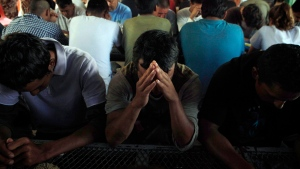 FILE - In this July 29, 2010 file photo, deportees pray as they gather for breakfast provided by the Kino Border Initiative in Nogales, Sonora, Mexico. (AP Photo/Jae C. Hong)