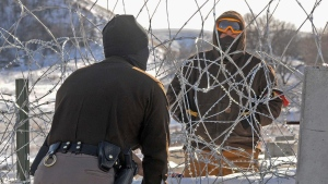 A law enforcement officer speaks to a protester against the Dakota Access Pipeline through a wall of razor wire on the Backwater Bridge over Cantapeta Creek on Thursday afternoon, Dec. 8, 2016. (Tom Stromme/The Bismarck Tribune via AP)