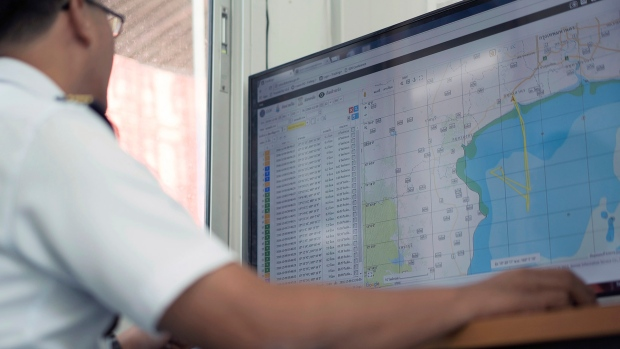 A Thai navy officer uses a new GPS tracking system to monitor locations of Thai fishing vessels in the waters off the coast of Samut Sakhon, Thailand, Friday, Dec. 9, 2016. The Thai Navy showed off new technology to monitor fishing boats Friday in a renewed effort to crack down on illegal fishing, forced labor, and corruption in the seafood industry. (AP Photo/Dake Kang)