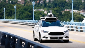 FILE - In this Thursday, Aug. 18, 2016, file photo, Uber employees test a self-driving Ford Fusion hybrid car, in Pittsburgh. (AP Photo/Jared Wickerham, File)