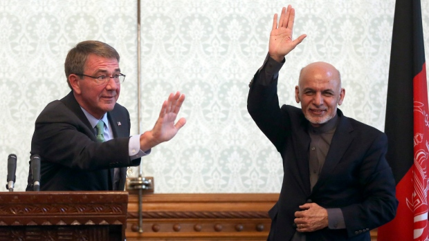 Afghan President Ashraf Ghani, right, and U.S. Defense Secretary Ash Carter, left, wave after a press conference at presidential palace in Kabul, Afghanistan, Friday, Dec. 9, 2016. (Massoud Hossaini/AP)