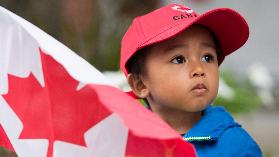 A young boy holds a flag as he watches the annual Canada Day parade in Montreal, Wednesday, July 1, 2015. (Graham Hughes/The Canadian Press)