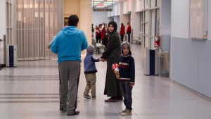 Members of a family of Syrian refugees look back at the arrival hall at the Welcome Centre at Toronto's Pearson Airport before boarding a bus to take them to a hotel as they land in Canada on Friday December 18, 2015. (Chris Young/The Canadian Press)