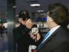 Holocaust-denying bishop Richard Williamson, left, raises his fist at a TV journalist as he passes through Buenos Aires Ezeiza International Airport in this image taken from television on Tuesday Feb. 24, 2008 (AP / TN- Todo Noticias)
