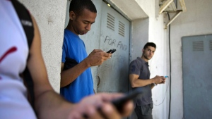 In this April 1, 2014 file photo, students gather behind a business looking for a Internet signal for their smart phones in Havana, Cuba. (AP / Ramon Espinosa, File)