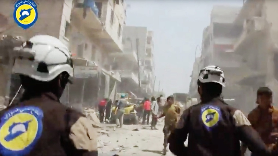 In this image made from video posted online by the Syrian Civil Defense White Helmets, Civil Defense workers run after airstrikes and shelling hit Aleppo, Syria, Sunday, April 24, 2016. (Syrian Civil Defense White Helmets via AP video)