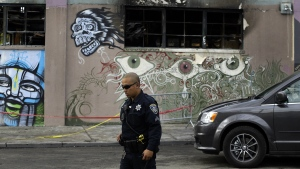 An Oakland police officer guards the area in front of the art collective warehouse known as the Ghost Ship in the aftermath of a fire on Friday, Dec. 9, 2016, in Oakland, Calif. (AP / Ben Margot)