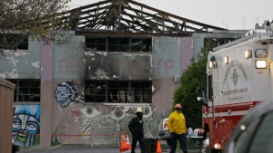 FILE - This Wednesday, Dec. 7, 2016 file photo shows Oakland fire officials walk past the remains of the Ghost Ship warehouse damaged from a deadly fire in Oakland, Calif. (AP Photo/Eric Risberg,File)